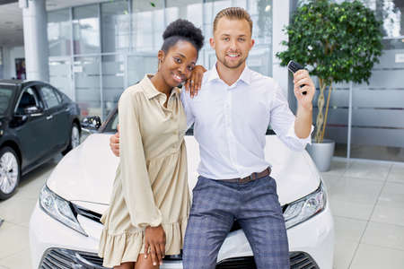 attractive woman and handsome guy happy with purchase in dealership, they got keys from their new white car they look at camera and smile