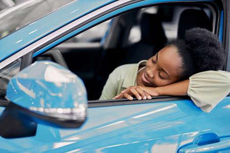 cute beautiful dark-skinned woman leaned on car, dreams about it, customer in dealership