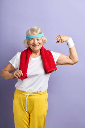 Elderly attractive woman with a happy, proud and satisfied expression on face, raising one hand, showing strength of her musculs, celebrating sport achievement. Reklamní fotografie