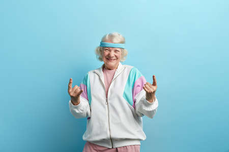 Cute hipster grandmother smiling and making rock sign against blue studio background Archivio Fotografico