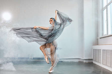 Full-size expressive photo of female ballet dancer dressed in grey-blue flowing fabric spinning on one leg on white y background.