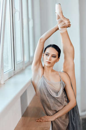 Beautiful professional ballerina in stage dress stretching leg in vertical split near window sill in class, preparing to performance