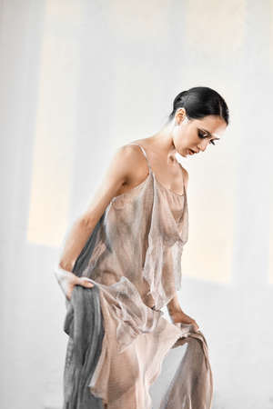 Young ballerina with a perfect body and gorgeous appearance dressed in stage long transparent robe or dress made from beige fishnet fabric.