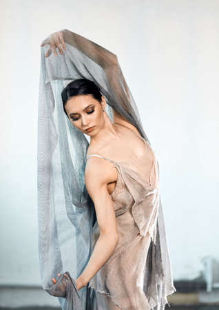 Beautiful ballerina in stage grey loose long transparent dress dancing modern ballet, performs artistic expressive movements with hands isolated on grey background