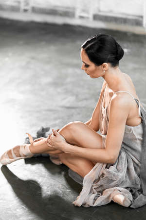 Ballerina putting on pointe shoes sitting on grey stone floor, being focused for upcoming performance Reklamní fotografie