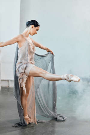 Fit graceful modern ballet dancer in grey scenic suit performing on pointes on light grey studio background.