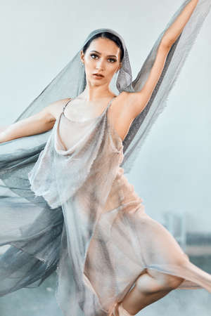 Beautiful dancing woman moving on stage in airy flying dress and cape on head. Modern ballet dancer dancing at studio. Art concept. Inspiration. Body Ballet.