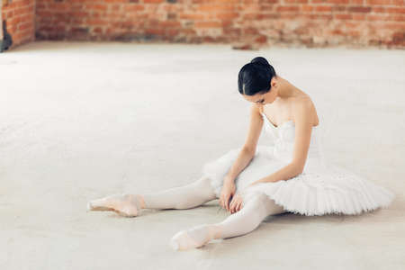 ballet dancer is tired after working out. young girl sitting with bend head on the floor during ballet classes. exhaustion, tiredness, difficulties in ballet