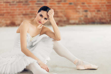 thoughtful awesome dancer in stylish white tutu looking at the camera, free time. leisure time, spare time