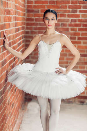 graceful good looking ballerina dressed in stylish tutu standing over red background, close up photo