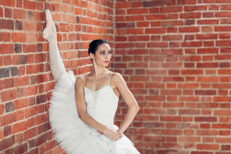 awesome slender ballerina in pointes doing near the loft wall. close up photo. copy space