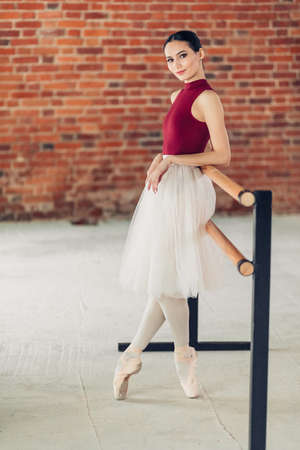 relaxed positive ballerina leaning on the barre and looking at the camera, full length photo.free time, spare time