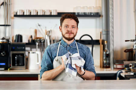 Skillful motivated worker, in nice apron, stands at bar counter drys steel coffee pot, looks at camera with kind look, expresses friendliness, service concept Stockfoto