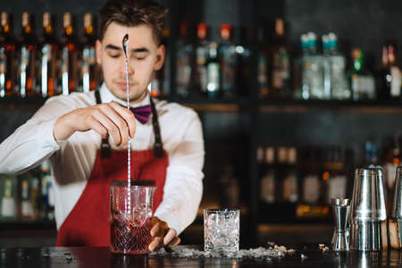 Young professional bartender mixing with long metal spoon cocktail in a glass standing at wooden bar counter with bottles of alcohol, blurry background.