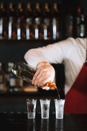 Expert barman in elegant uniform working at night party at popular nightclub, pouring gin or vodka in frosted short glasses