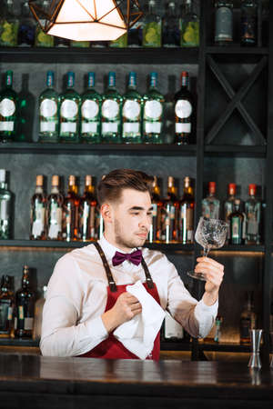 Young handsome smiling barman in bar interior wiping vine glasses. Professional bartender portrait at work in night club cleaning stemware while waiting for orders.