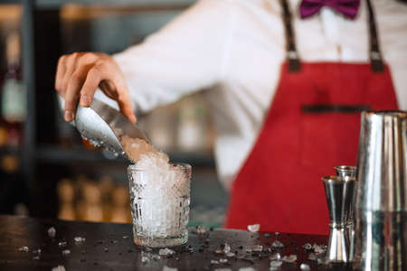 Bartender in the white shirt and red apron adding ice crumbs into an empty cocktail glass on the bar counter at restaurant