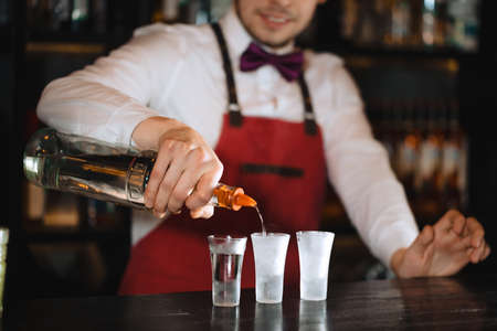 Professional male bartender serving the order, pouring alcoholic drink in a row of shot frozen glasses in a night club