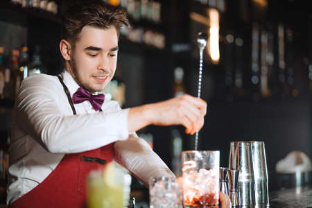 Barman holding a long spoon and glass filled with ice cubes and red drink mixing the beverage on the bar counter of night club Standard-Bild