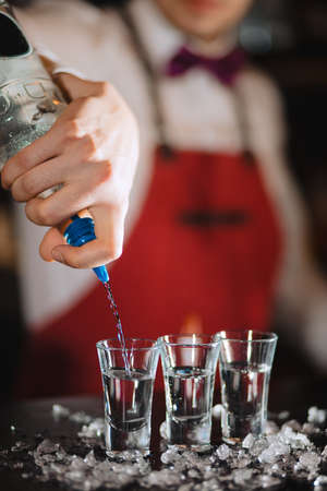 American bartender completing an order, focus on transparent short glasses standing on shaved or crushed ice. Night Life, alcohol drinks, luxury night club. Stockfoto