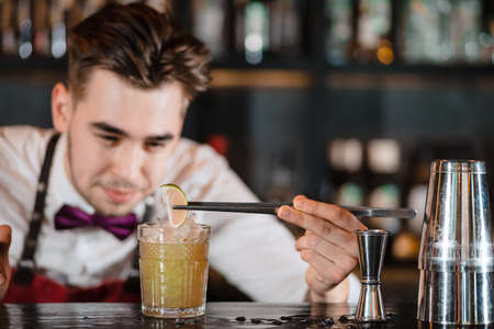 Bartender finishes decoration of his cocktail with ice cubes and lime slice using tweezers.