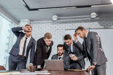 surprised caucasian business team cosisted of men in elegant suits, look at laptop surprisingly, stay in shock after results. isolated in modern office