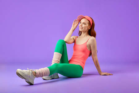 Fit satisfied red-headed girl wears sportsclothes, keeps hand on sun cap, has glad expression, sits on the floor, feels relaxed and refreshed, full of energy after aerobics workout