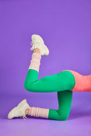unrecognizable sporty woman lifts bent leg up on all fours, works out abdominals and butt muscles, shows excellent curves and shape, wears green leggins, pink bodysuit and white sport shoes Reklamní fotografie