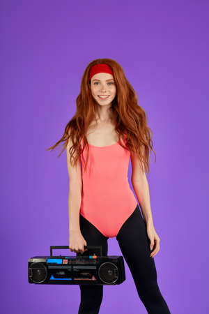 female shaping trainer with long red hair, glowing healthy skin and pretty freckles with curves and muscules, stands during break, feels relaxed and positive, holds in one hand portable audio player