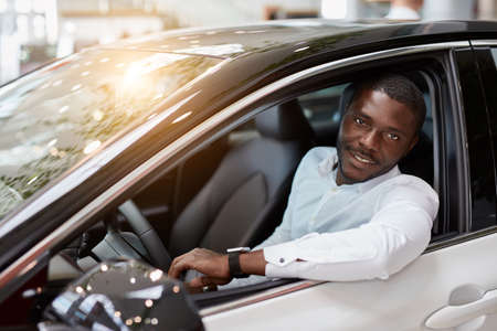 handsome rich african man try himself behind the wheel of new automobile, man likes it, gong to buy Foto de archivo