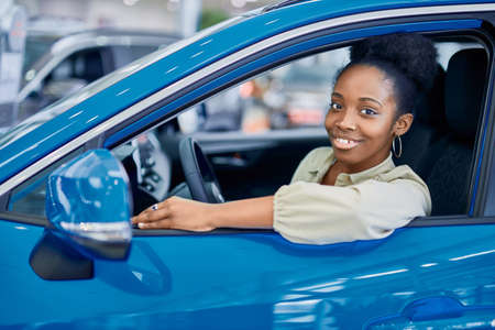 satisfied african woman behind the wheel of blue automobile represented in cars showroom, she looks at camera and smile Stock Photo
