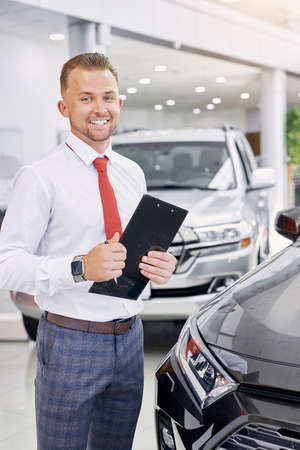 confident caucasian smiling car dealer at work, man in white formal shirt ready to talk about cars, automobiles and their chaacteristics to customers