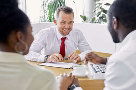 young caucasian professional sales agent and afro american clients have friendly conversation in dealership, customers came to buy new car