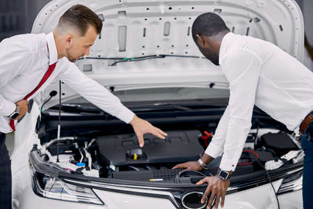 african customer and caucasian salesman opened the car hood and discuss all the nuances concerning the car. in dealership