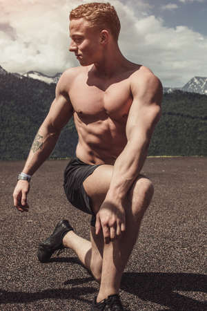 Young handsome blonde bodybuilder showing muscles shape outdoors, kneeling in show pose on the artificial sand field, Man and Beauty, Sport, Bodybuilding concept.