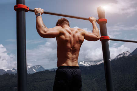 Naked torso athlete man training pull ups in amazing nature mountains landscape. Strength training fit male working out exercising outdoors in summer doing pull-ups and chin-ups on horizontal bar. Archivio Fotografico