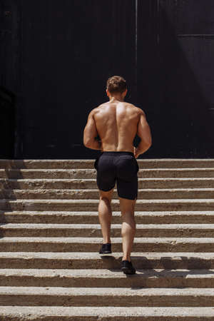 Full length of young African man in sports clothing running down the stairs while exercising outdoors