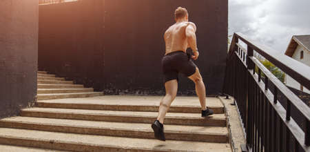 American muscular man in jogger shorts running upwards with efforts on the high and long distance staircase, sport, fitness, jogging, healthy lifestyle concept.