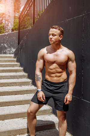 Crossfit male trainer with muscular naked torso stand near grey k wall background. Sexy torso caucasian athlete. Attractive and confident. Strong chest biceps emphasize masculine sexuality.