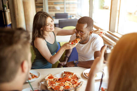 Young multiracial diverse colleagues eating pizza during their lunch time at office pizzeria, playing team building game, feeding his partner with tasty pizza