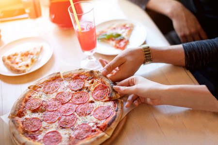 Selective focus of fresh just baked hot selfmade pizza with salami, tomato, cheese on wooden table background.