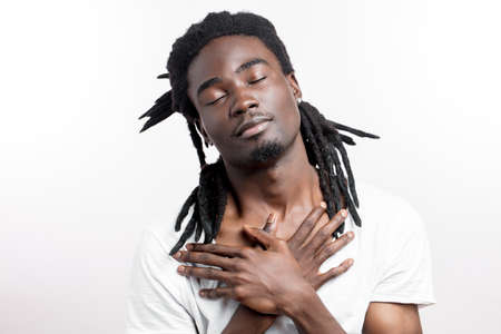 Dreaming african man with dreadlocks on white background with hands on chin or chest and closed eyes