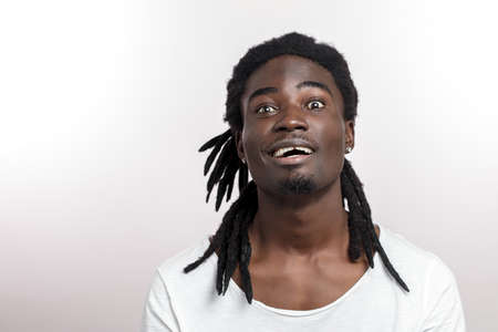 Portrait of a handsome happy young african man with dreadlocks on white background Stock fotó