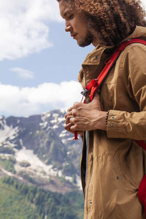 Young long curly haired man standing on summer mountains background and enjoying Stockfoto