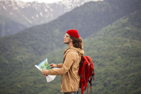 Tourist in yellow jacket with map on rocks somewhere in mountains
