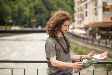 Young tourist with route maps looking for a way in city. search landmarks