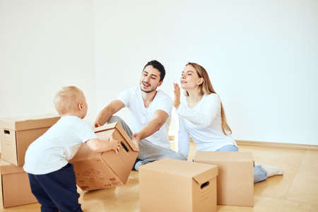 Family with little boy unpacking moving cardboard boxes at new home