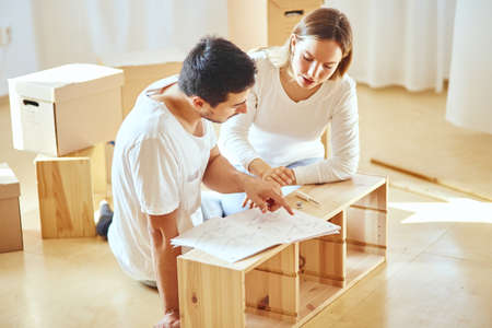 Young couple installing furniture in new house with instruction