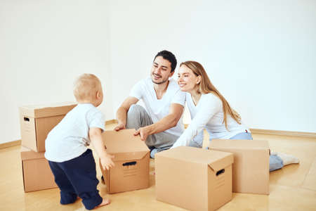 Family, parents and son, unpacking boxes and moving into new home, baby help for parents