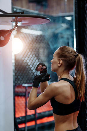 sporty blond woman training speed hits on small boxing bag